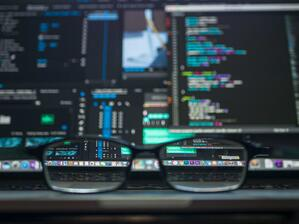 glasses in front of multiple computer screens, comparing moodle hosting provider and self-hosting