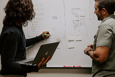 image man and woman strategizing with a whiteboard